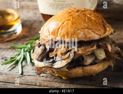 Burger with mushrooms, fried onions and cheese on rustic background - Stock Photo