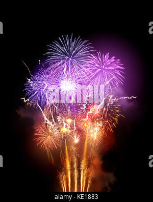 A large bright fireworks display event with golden orange and purple rocket breaks. - Stock Photo
