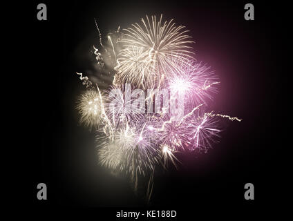 A large bright fireworks display event with gold and pink rocket breaks. - Stock Photo