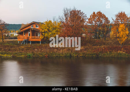 riverside cottages around autumn trees on lake - Stock Photo
