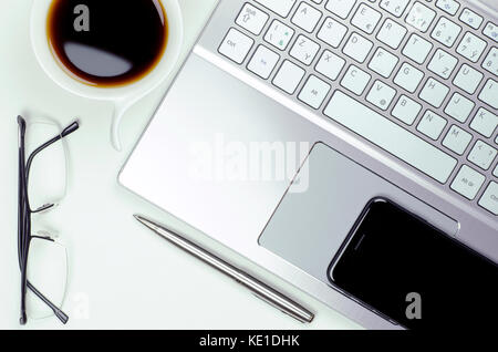Close-up view of still life with laptop and smartphone, pen and glasses next to a cup of coffee on a white background - Stock Photo