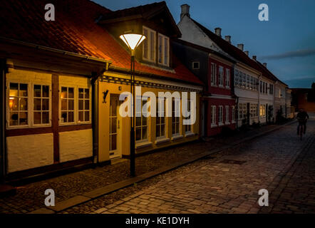 night view of traditional cobbled street old houses lit by single street lamp Odense Denmark - Stock Photo