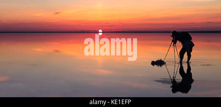 Silhouette of alone man takes a picture of a vibrant sunset reflected in shallow waters of solt lake. Banner size - Stock Photo