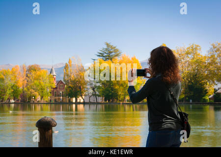Young woman taking a photo of autumn colors and reflection on the Puigcerda's pond water - Stock Photo