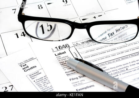 Federal income tax 1040 form on a calendar with the 15th noted on it with a pen and glasses on top of it. - Stock Photo