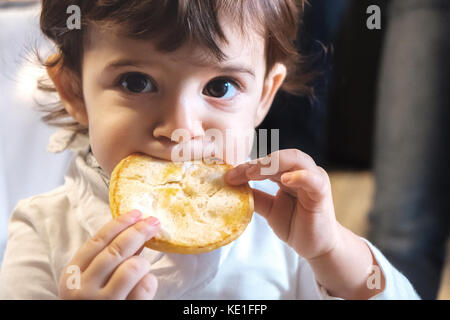 baby child eat carbohydrates -  newborn eating face closeup portrait - unhealthy diet for kids - Stock Photo