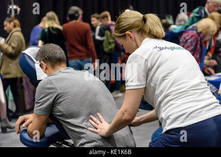 A woman gives a massage at a vegan festival. - Stock Photo