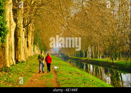 couple walking dog on towpath, Lalinde Canal at Lalinde, Dordogne Department, Aquitaine, France - Stock Photo