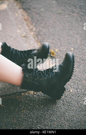 Woman wearing black lace up boots sitting in the street, UK - Stock Photo
