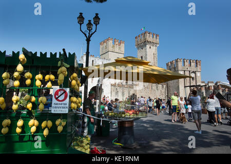 Sirmione, Italy. Colourful view of a fresh fruit vendor with the entrance to Scaliger Castle in the background. - Stock Photo