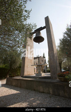 Sirmione, Italy. An Italian bell war memorial, with the ancient Chiesa di San Pietro in Mavino church in the background. - Stock Photo