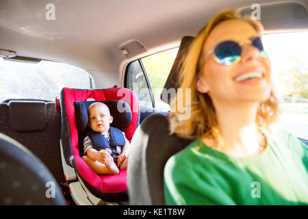 Young mother with her little son in the car. A woman driving and baby boy sitting in a car seat. - Stock Photo