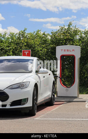 PAIMIO, FINLAND - JUNE 4, 2016: White Tesla Model S electric car is being charged at Tesla Supercharger station. - Stock Photo