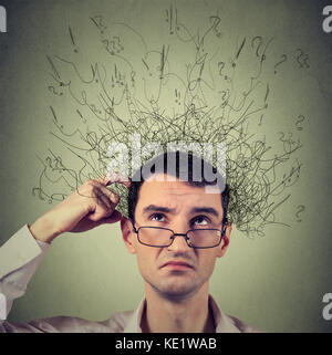 Closeup portrait young man scratching head, thinking daydreaming with brain melting into many lines question marks - Stock Photo
