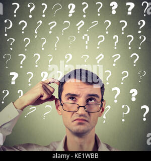 Portrait confused thinking young man in glasses bewildered scratching his head seeks a solution looking up at many - Stock Photo