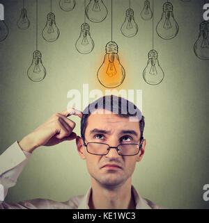 Portrait thinking man in glasses looking up with light idea bulb above head isolated on gray wall background - Stock Photo