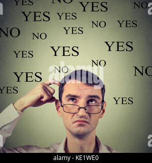 Headshot thinking perplexed young man in glasses with yes or no choice looking up isolated on gray wall background - Stock Photo