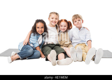 happy multiethnic children sitting together isolated on white - Stock Photo