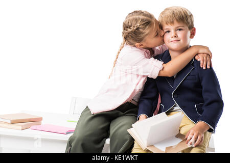 cute little girl kissing boy holding book and looking at camera isolated on white - Stock Photo