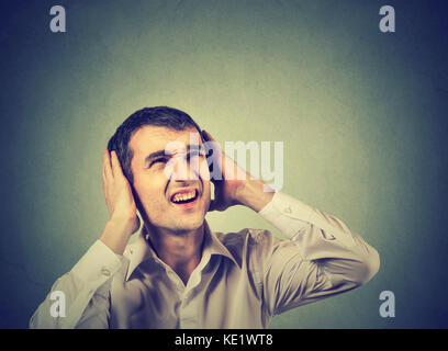 Young annoyed, unhappy, stressed man covering his ears, looking up, stop making loud noise, giving me headache isolated - Stock Photo