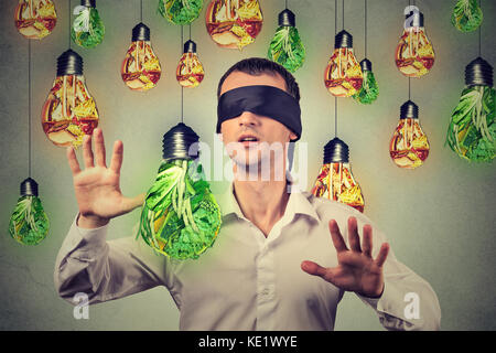 Blindfolded young man walking through light bulbs shaped as junk food and green vegetables isolated on gray wall - Stock Photo
