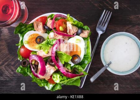 Overhead photo of tuna salad with rose wine, fork, sauce - Stock Photo
