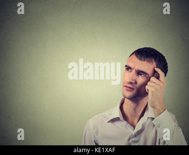 Closeup portrait man scratching head, thinking deeply about something, looking up, isolated on grey wall background. - Stock Photo