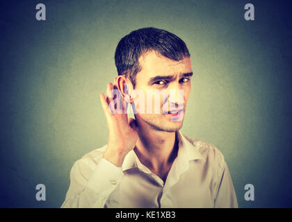 Unhappy hard of hearing man placing hand on ear asking someone to speak up or listening to bad news, isolated on - Stock Photo