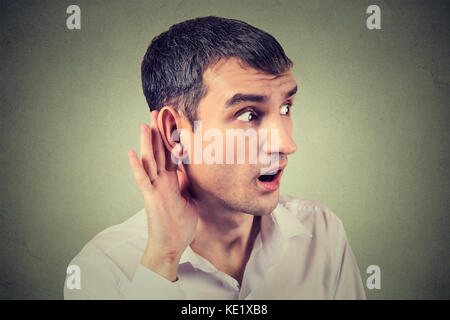 Closeup portrait hard of hearing man placing hand on ear asking someone to speak up or listening carefully to a - Stock Photo