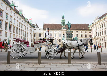 VIENNA, AUSTRIA - AUGUST 28: Tourists in a horse-drawn carriage called Fiaker at the imperial Hofburg palace in - Stock Photo