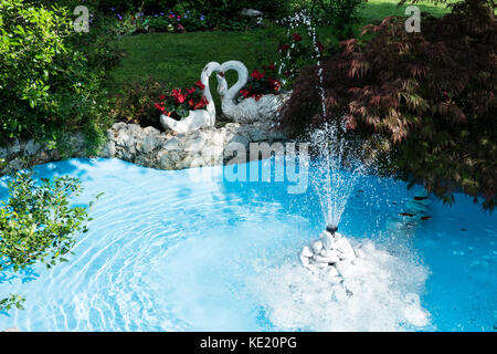 Ornamental pond and water fountain in a beautiful lucid flowering green garden and swans - Stock Photo