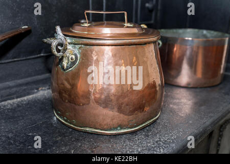 Victorian copper casserole pan on a black antique gas stove in a traditional English Victorian kitchen, UK - Stock Photo