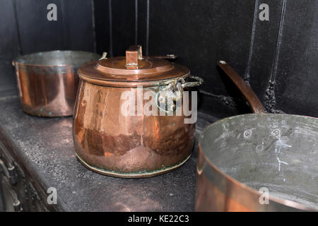 Victorian copper casserole pan on a black antique gas stove in a traditional English Victorian kitchen - Stock Photo