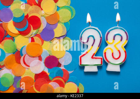 Number 23 celebration candle with party confetti - Stock Photo