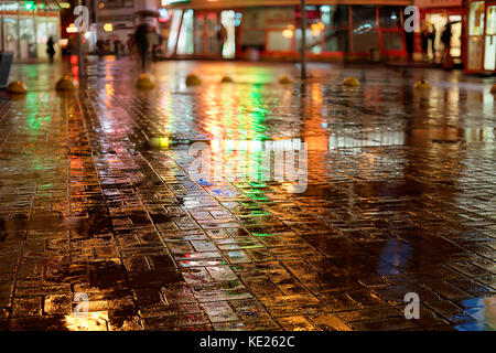Rainy night in the city. Wet street, colored lights reflection and blurred silhouettes with umbrellas. - Stock Photo