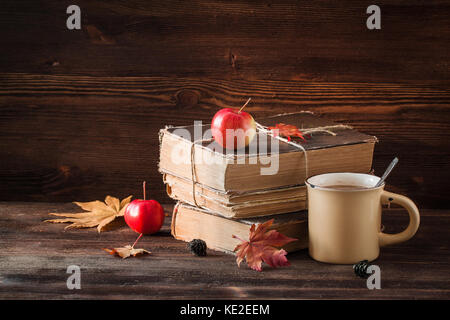 Autumn still life with old books, apples, maple leaves on the wooden background. Toned. - Stock Photo