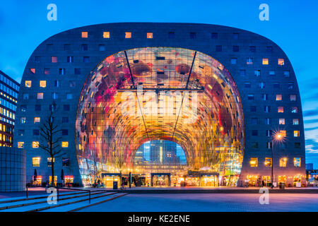 Market Hall in the Blaak district of Rotterdam, Netherlands at dusk. It is a residential and office building with - Stock Photo