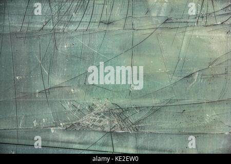 Damaged, broken glass sheet with black cracks on green background - Stock Photo