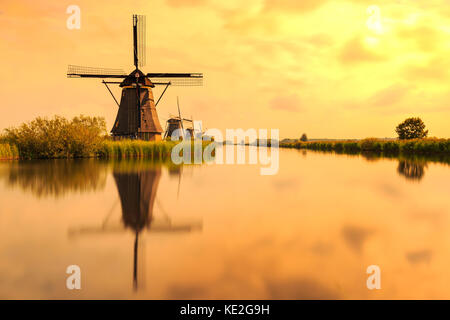 Traditional Dutch Windmills Kinderdijk, World Unesco heritage, on a sunny day late summer. Reflection visible on - Stock Photo