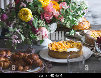 Festive table with big bouquet, homemade cakes and scones - Stock Photo