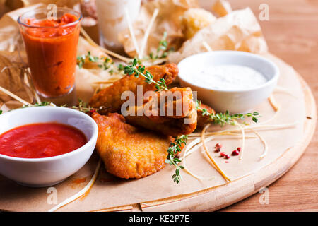 Spicy baked chicken wings with appetizers and sauces on a round wooden Board - Stock Photo