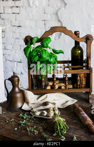 The bottle of wine, Basil and ingredients for cooking in rustic kitchen - Stock Photo