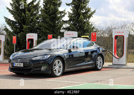 PAIMIO, FINLAND - APRIL 29, 2016: Black Tesla Model S electric car which operates as taxi cab is being charged at - Stock Photo