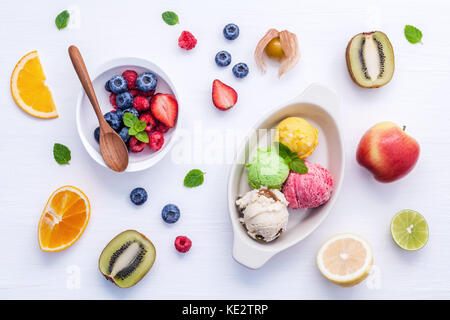 Colorful ice cream with mixed berry and various fruits raspberry ,blueberry ,strawberry ,orange slice , halve kiwi - Stock Photo