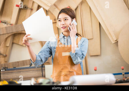 Young smiling female woodworker with blueprint talking on cellphone - Stock Photo