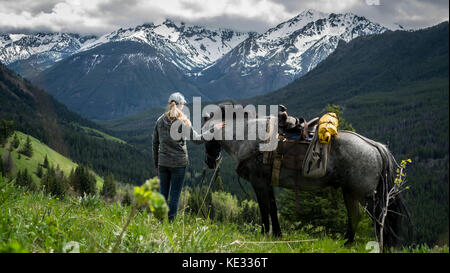 A female guide and her blue roan gelding travelling together through alpine meadows in the South Chilcotin Mountain - Stock Photo