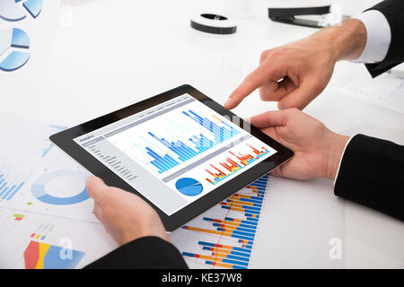 Close-up Of Businesspeople Comparing Graphs On Digital Tablet In Office - Stock Photo