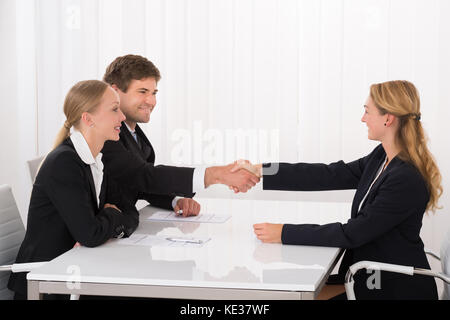 Confident Happy Young Male Applicant Shaking Hands With Manager During Interview - Stock Photo