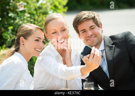 Young Happy Male And Female Businesspeople Taking Selfie With Cellphone - Stock Photo