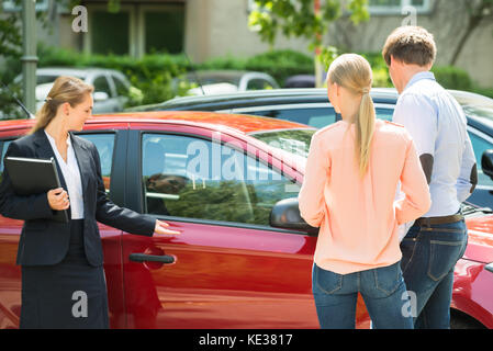 Confident Young Female Dealer Showing New Red Car To Couple - Stock Photo